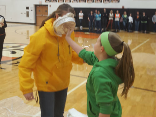 STUDENTS GETS TO PUT A PIE IN THE FACE OF MRS. GOUBEAUX AT PI DAY ASSEMBLY