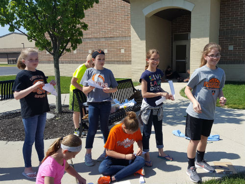 STUDENTS TAKE TURN THROWING THEIR PAPER AIRPLANES FOR SCIENCE PROJECT