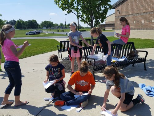 STUDENTS TAKING DISTANCE MEASUREMENTS FOR THEIR ROCKETS