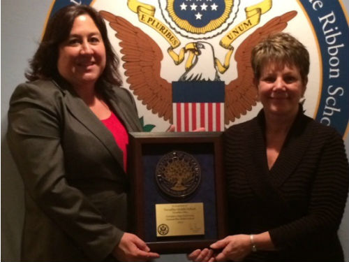 MRS OSTERFELD AND MRS. HAYES RECEIVING THE BLUE RIBBON AWARD ON BEHALF OF THE MIDDLE SCHOOL